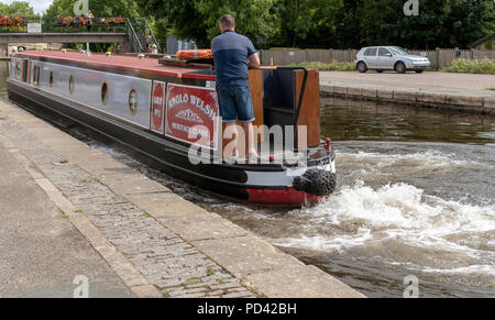 Llangollen Canal at Trevor Basin, Denbighshire, North East Wales. A holiday hire canalboat alongside the wharf. - Stock Photo