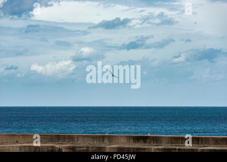 horizon with the clouds and blue sea view from castelsardo harbour on the italian island of sardinia or sardegna - Stock Photo