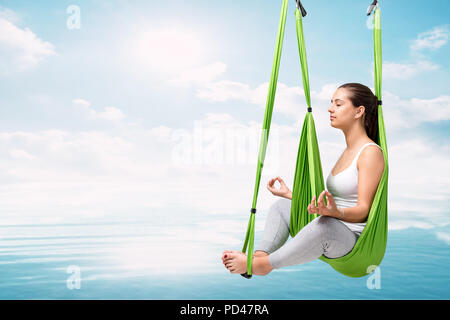 Conceptual portrait of young woman doing aerial yoga over lake. Girl in hanging antigravity hammock about to touch water surface. - Stock Photo