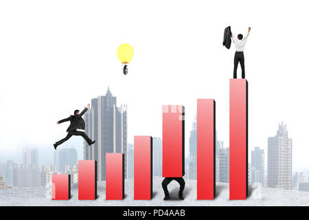 Businessman running and jumping on red bar chart, with one lifting, one cheered, one in lamp balloon, city background - Stock Photo
