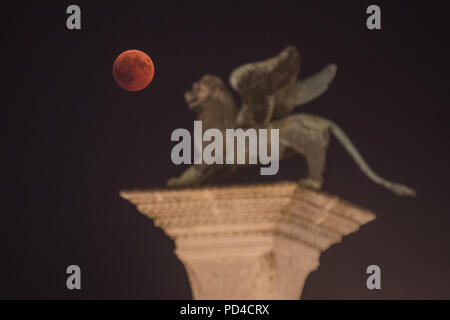 The total lunar eclipse is seen close to the Lion of Venice, in St. Mark square. - Stock Photo