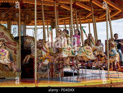 Children on a Steam Galloping horse carousel, fairground ride at a steam fair. England - Stock Photo