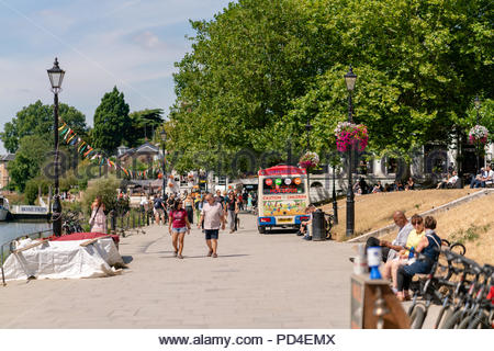 Locals going out during for lunch time breaks enjoying the summer heat along the riverside in Richmond-upon-thames - Stock Photo