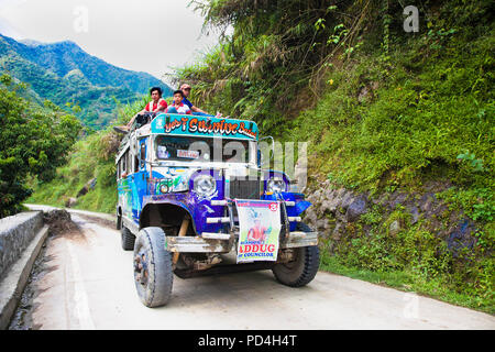 BATAD, PHILIPPINES-MARCH 31, 2016:  Local public transport jeepney driving fast along a mountain road in  province  Banaue on March 31, 2016. Northern - Stock Photo