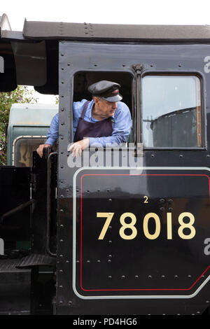 Engine driver on the footplate of No.78018 British Railways Standard Class 2 steam locomotive and looking out of the cab - Stock Photo