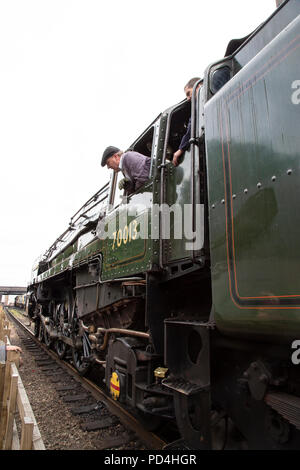 Engine driver and fireman looking out of the cab on B.R. Steam Locomotive 70013 'Oliver Cromwell' 7P6F Britannia Class - Stock Photo
