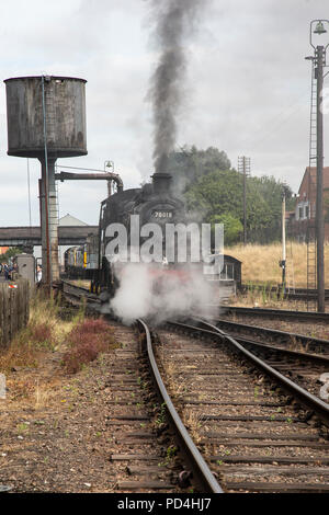 British Railways Steam locomotive 4MT number 78018 taking on water and belching steam and black smoke on the sidings at Loughborough Heritage Railway - Stock Photo