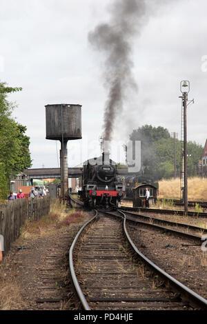 British Railways Steam locomotive 4MT number 78018 belching black smoke on the sidings at Loughborough Heritage Railway - Stock Photo