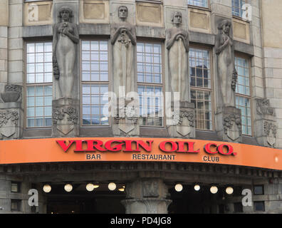 Contrasting styles in Helsinki Finland,, beautiful art nouveau facade decoration opposed by glaring orange and red restaurant sign - Stock Photo