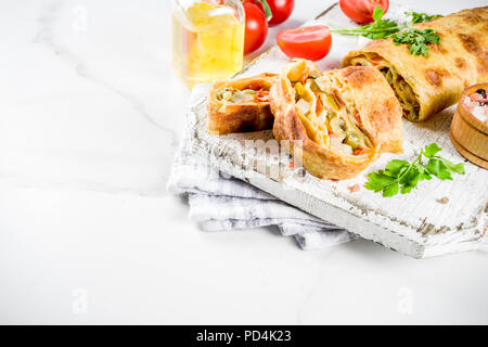 Vegetable savory strudel, homemade autumn baking, with tomatoes, bell pepper, mushrooms, wooden background copy space - Stock Photo