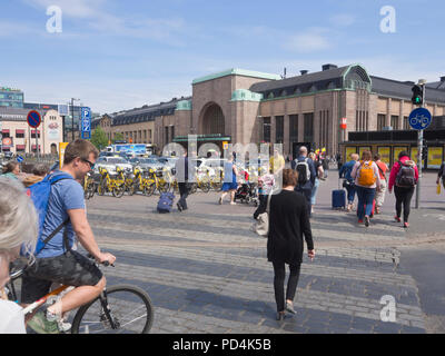 Busy pedestrian crossing in front of the Central Railway Station in Helsinki Finland - Stock Photo