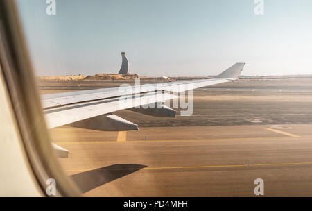 Aerial view out of airplane window while taking off from the runway of the airport during sunset - Stock Photo