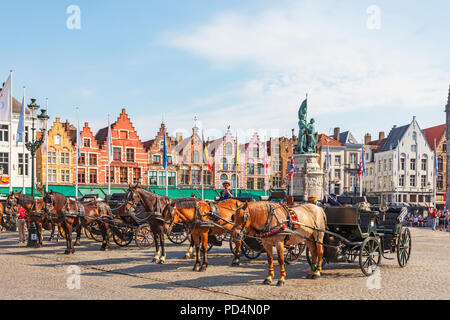 Horse and traps in Markt Square, Bruges used for taking tourists on a  city tour, Bruges, Belgium - Stock Photo