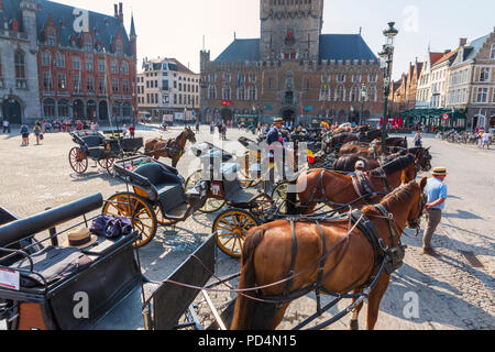 Horse and traps lined up in Markt Square near Bruges Belfry Bruges, Belgium. The horse and traps are used to take tourists on city tours - Stock Photo