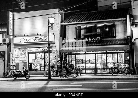 Kyoto, Japan.  A man on a bicycle near the store on Gion street at night - Stock Photo