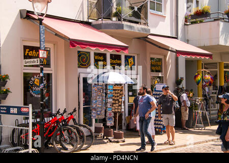Warnemunde, Germany - June 8, 2018: A view of tourists walking past a souvenir shop and a rental bicycle stand on a sunny day in this tourist town - Stock Photo
