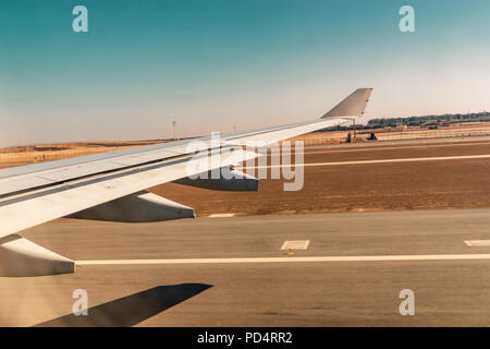 Aerial view out of airplane window while taking off from the runway of the airport with desert and blue sky - Stock Photo