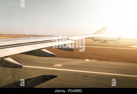 Aerial view out of airplane window while taking off from the runway of the airport - Stock Photo