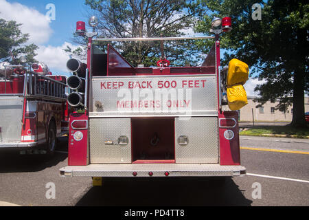 Back of red fire truck with the words Keep Back 500 Feet and Members Only panted in red on the chrome in the back - Stock Photo