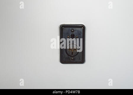 Old fashioned bakelite power socket with on/off switch on a white plaster wall - Stock Photo