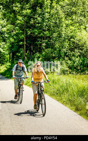 People enjoying a leisurely bicycle ride in rural Austria on a summer's day. - Stock Photo