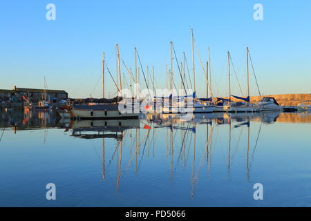 Sailing boats reflected on the water in Lyme Regis harbour known as The Cobb - Stock Photo