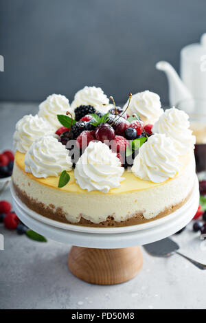 Classic vanilla New York cheesecake decorated with whipped cream and fresh berries - Stock Photo