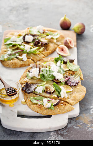 Fall flatbread pizza with fresh figs, arugula and goat cheese - Stock Photo
