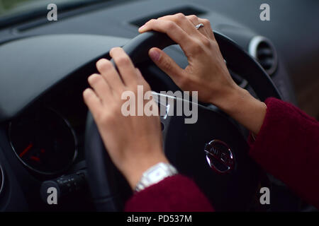 Close up shot of female hands driving - Stock Photo
