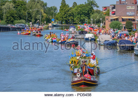 Colorful parade of small, flower-decorated boats with cheerful dressed up children. - Stock Photo