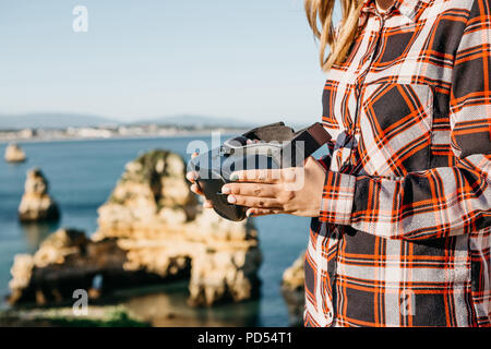 The girl is holding virtual reality glasses and is going to put them on. Conceptual photography of virtual travel or tourism. Modern technology in everyday life. - Stock Photo