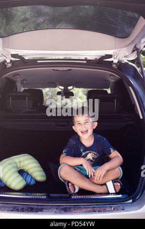 Little kid boy sitting in car trunk just before leaving for trip - Stock Photo