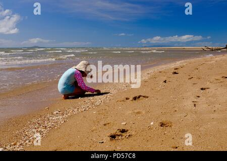 Young child playing on a deserted tropical beach, Toomulla QLD, Australia - Stock Photo