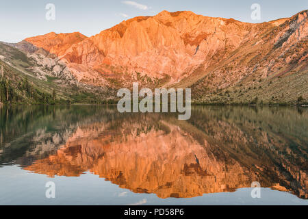 Sunrise casts golden light on mountain peaks reflected in the calm waters an alpine lake - Convict Lake in the Sierra Nevada mountains of California - Stock Photo