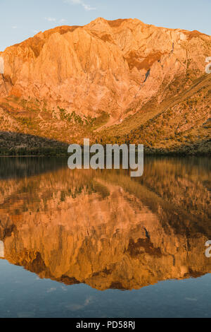 Sunrise casts golden light on mountain peaks reflected in an alpine lake - Convict Lake in the eastern Sierra Nevada mountains of California - Stock Photo