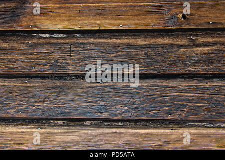 Weathered rustic wood plank background texture with yellow, black, and brown color tones - Stock Photo