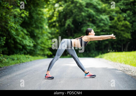 Athletic woman warming up before a workout standing facing the early morning rising sun on a rural road doing stretching exercises - Stock Photo