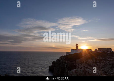 Sunset with the Lighthouse of Cabo de São Vicente, Cape St. Vincent, and lighthouse, Algarve, Portugal. - Stock Photo