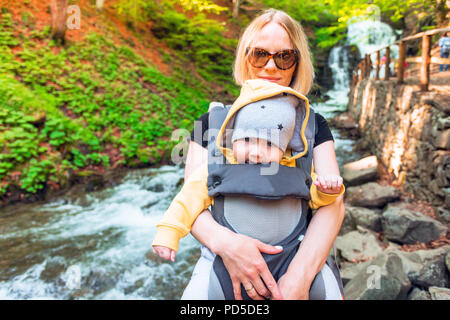 Happy mother with little boy travelling in backpack. Hiking adventure with child on spring in mountains. Vacations journey with infant carried in fron - Stock Photo