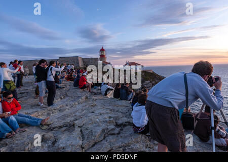 Crowd of tourists gathering for the sunset at Cabo de São Vicente, Cape St. Vincent, and lighthouse, Algarve, Portugal. - Stock Photo
