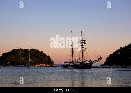The harbour at Lakka, Paxos, Greece at sunrise, with the topsail schooner Rhea at anchor - Stock Photo