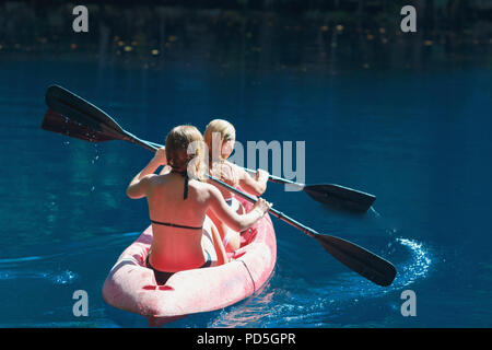 two girls kayaking on a blue lake, Laguna Dudu, Dominican Republic - Stock Photo
