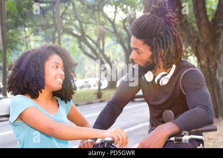 Biker is talking to black woman on sidewalk. Friends are chatting in wooded street. - Stock Photo