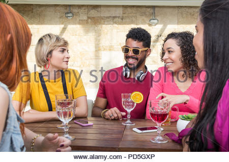 Group of young people hanging out, having fun at restaurant outside. College students partying together at cafe bar outdoor. Spring, warm, togethernes - Stock Photo