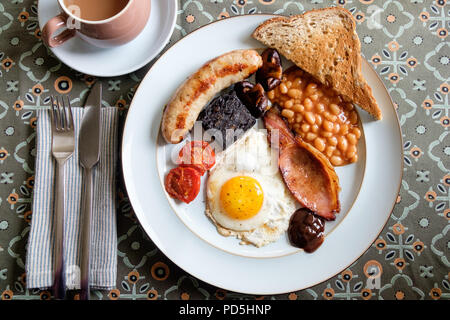 A homemade full English breakfast with egg, bacon, Cumberland sausage, black pudding, baked beans, tomato, mushrooms, toast and a cup of tea. - Stock Photo