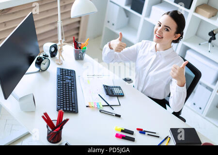 A young girl in the office sits at a table, works by documents and shows a class sign. - Stock Photo