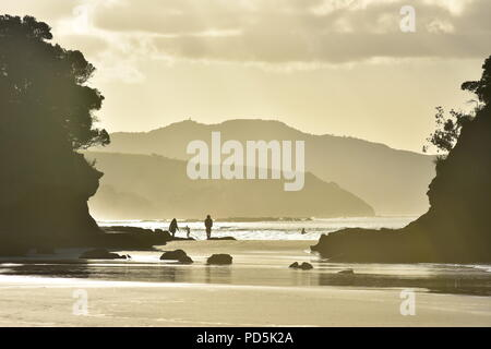 Flat sandy oceanic beach reflecting bright back light between rocky cliffs with hills in background. - Stock Photo
