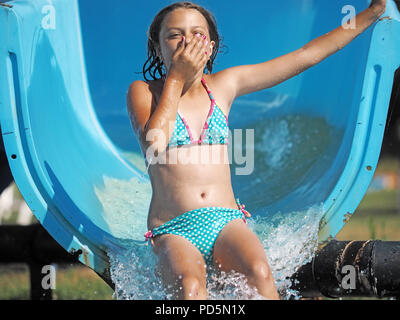 Little girl playing in a water park - Stock Photo
