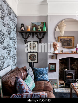 Zingara wallpaper in Ceulean Sea by little Greene in cosy sitting room with leather sofa and woodburning stove. The palm print cushion is by House of  - Stock Photo
