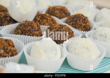 Chocolate and coconut cake on a round blue plate in cafe - Stock Photo